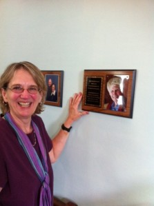 Kristen Jarvi in front of the plaque honoring her mom, Betty Jarvi. Other plaques not visible are honoring Jane & Rob Buswell & Evelyn Warren. Photo by Annie Clarke.